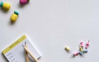colorful pins, erasers and a weekly planner that can be used to plan a creative break